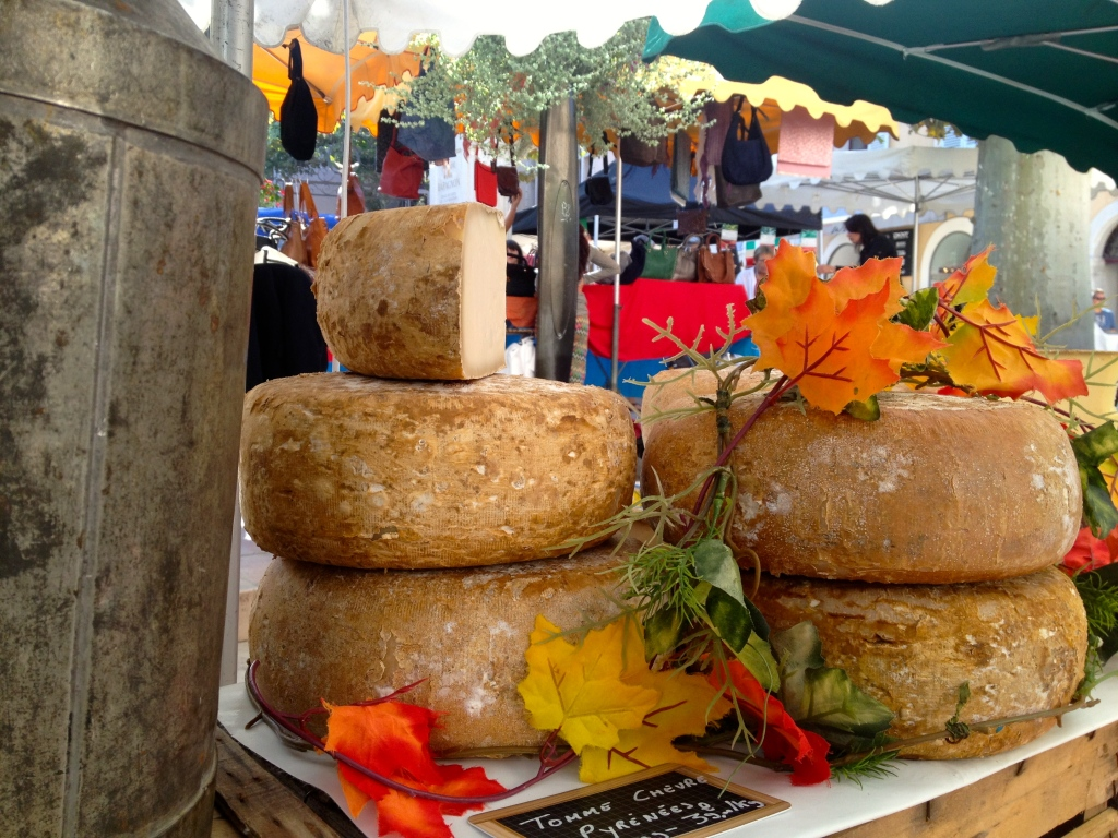 The cheese man decorates his wheels of cheese with autumn leaves